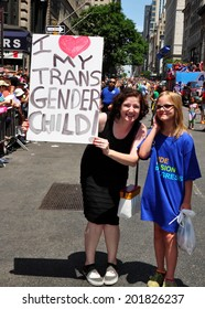 NYC - June 29, 2014:  Mother holding a sign with her child at the 2014 Gay Pride Parade on Fifth Avenue