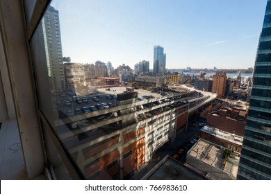 The NYC Port Authority's rooftop parking lot as seen through an adjacent building's window.