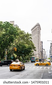 NYC / USA - July 2019: New York City architecture Flatiron building near Madison Square Park in Manhattan. In the foreground is a traditional yellow New York City taxi