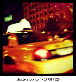 NYC yellow cab in motion at night in Manhattan with Instagram effect filter.
