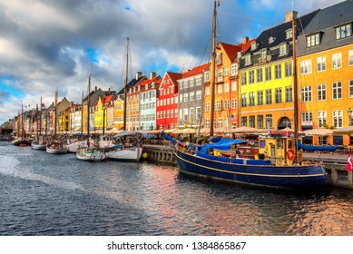 Nyhavn area of popular bar and restaurant at beautiful blue sky, with colorful facades of old houses and old ships in the Old Town of Copenhagen, capital of Denmark.