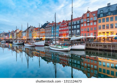 Nyhavn with colorful facades of old houses and old ships in the Old Town of Copenhagen, capital of Denmark.