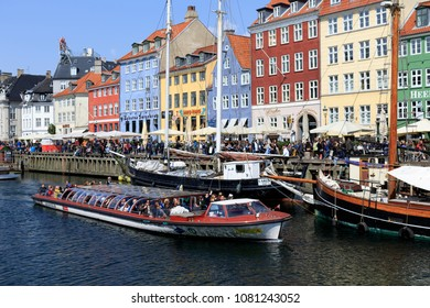 Nyhavn, Copenhagen, Denmark. 30 April, 2018. Nyhavn is a tourist magnet with its cafes, colorful houses, canals, boats and relaxed atmosphere. In the foreground a canal sightseeing boat.
