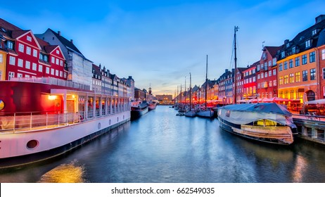 Nyhavn with its picturesque harbor with old sailing ships and colorful facades of old houses in Copenhagen, Denmark.