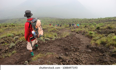 Nyiragongo volcano, Goma, DR Congo - September 2017: Guide looking down mountain to tourists walking up Nyiragongo volcano