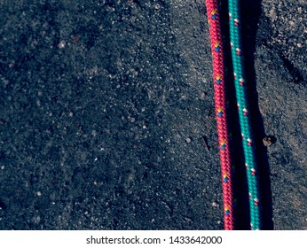 Nylon rope on gray rocky background. Climbing equipment. Twisted old fashion rope fixed on rock. Detail of rope.