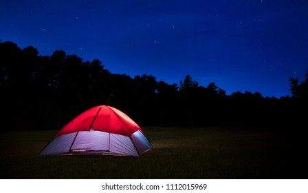 Nylon tent pitched in a field with bright stars above