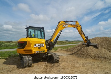 Nymindegab Strand, Denmark - June 20, 2020: colorful, clean and new yellow digger of the type JCB stands on sandy ground nxt to a small hill of gravel