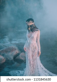 Nymph, walks in the river which was tightened by a thick, impenetrable fog. She has a white vintage, lacy dress. Feast of Ivan Kupala. The girl turned her face away from the camera.