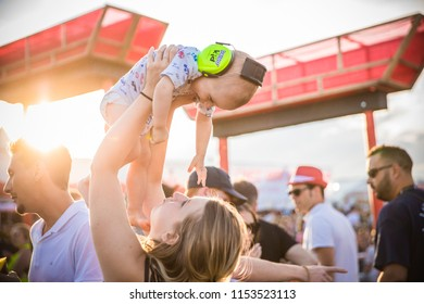 Nyon, Switzerland - 18 July 2018: Young mother having fun with her baby at sunset at Paleo Festival