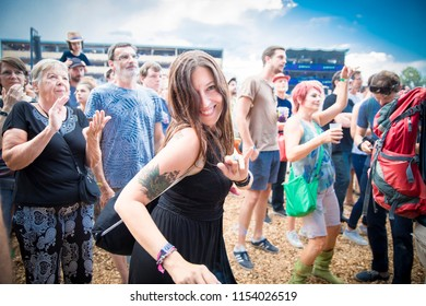 Nyon, Switzerland - 19 July 2018: young woman in the audience dancing during concert of Serbian rock and punk band Emir Kusturica and the No Smoking Orchestra at Paleo Festival
