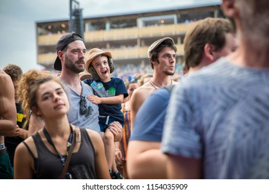 Nyon, Switzerland - 19 July 2018: young boy watching amazed the concert of Serbian rock and punk band Emir Kusturica and the No Smoking Orchestra in his father's arms at Paleo Festival