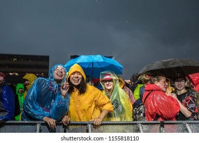 Nyon, Switzerland - 20 July 2018: people in the audience with colorful raincoat waiting under the pouring rain the concert of American rock and roll band Nathaniel Rateliff & The Night Sweats at Paleo