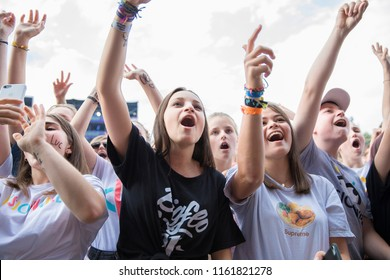 Nyon, Switzerland - 21 July 2018: young girls, fan with name of artist painted on their face, cheering and filming concert of French Rap band BigFlo & Oli at Paleo Festival