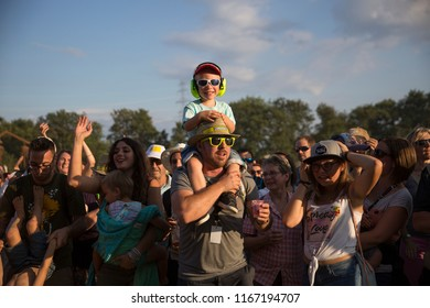 Nyon, Switzerland - 22 July 2018: Child on his father shoulders dancing together at pop up concert of Italian Rock band Giufa at Paleo Festival