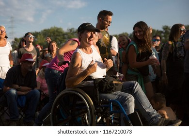 Nyon, Switzerland - 22 July 2018: woman on a wheelchair in the audience dancing, clapping and cheering at pop up concert of Italian Rock band Giufa at Paleo Festival