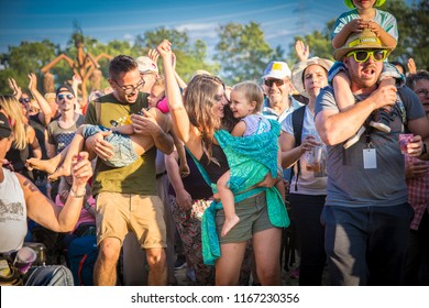 Nyon, Switzerland - 22 July 2018: family dancing with mother and father dancing with their children in their arms at pop up concert of Italian Rock band Giufa at Paleo Festival