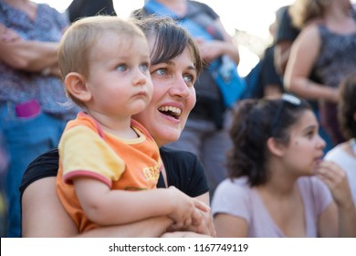 Nyon, Switzerland - 22 July 2018: mother and small child in the audience watching a theater show with a big smail at Paleo festival