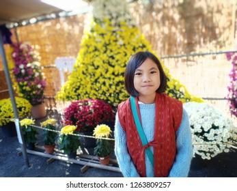 Nyonya smilingly face. Flowers background.