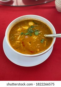 Nyonya traditional style in seafood spicy soup well known as 'Tomyam SEafood', with fresh shrimp and other ingredients in white bowl