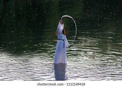 Nysterious Nymph dressed with withe dress walking in water