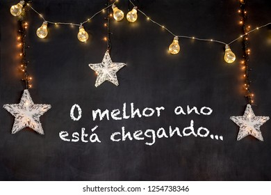 """""""o melhor ano está chegando"""" in portuguese means """"the best year is coming"""" in black background with white stars and yellow light"""