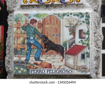 """O Pedrouzo, A Coruna / Spain - 06/12/2015: Artistic design ceramic tile on a fence by rural home, warning about a dangerous dog """"Perro peligroso"""""""
