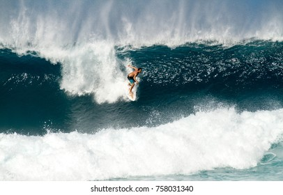 Oahu, Hawaii - 2/16/17: A lone surfer rides a Large wave in the pipeline section of the north shore coast on the island of Oahu, Hawaii.