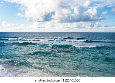 OAHU, HAWAII - NOVEMBER 13, 2017: Five surfers trying to catch waves on a beautiful day at Sunset Beach located on the North Shore