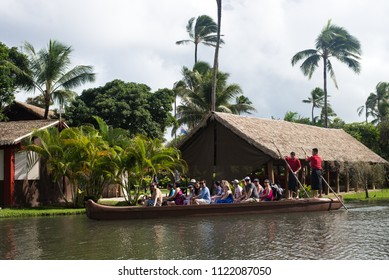 OAHU, HAWAII - NOVEMBER 14, 2017: Tourists in the Polynesian Cultural Center, are paddled down the stream on a canoe by their tour guide.