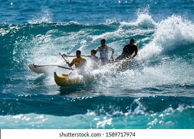 OAHU, HI / USA - NOVEMBER 17, 2018: Two fathers with kids surf canoe in Hawaiian waters