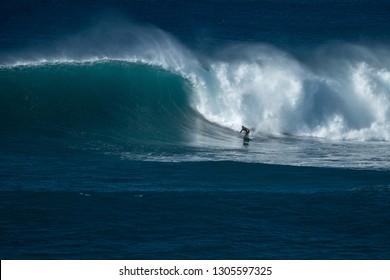OAHU / USA - 05 DECEMBER 2018: Extreme surfer rides gigantic ocean wave at Waimea Bay surf spot. The North Shore of Oahu, Hawaii