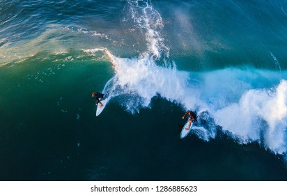 OAHU / USA - 13 NOVEMBER 2018: Two surfers ride the wave simultaneously. Example of violation of the surf etiquette