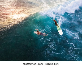 OAHU / USA - 15 NOVEMBER 2018: Surfer rides the ocean wave on the longboard while another surfer paddles and passes this wave. Oahu, Hawaii