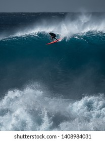 OAHU / USA - DECEMBER 05, 2019: Surfer rides giant wave at the famous Waimea Bay surf spot located on the North Shore of Oahu in Hawaii