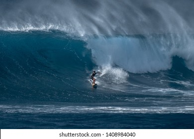 OAHU / USA - DECEMBER 05, 2019: Surfer rides furious wave at the famous Waimea Bay surf spot located on the North Shore of Oahu in Hawaii