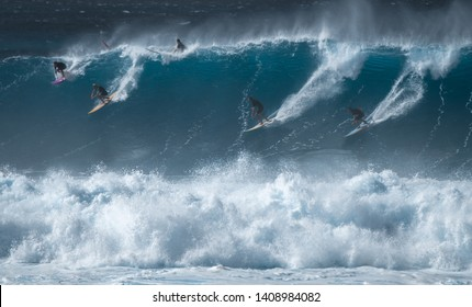 OAHU / USA - DECEMBER 05, 2019: Four surfers share the giant wave at the famous Waimea Bay surf spot located on the North Shore of Oahu in Hawaii