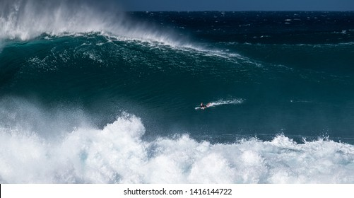 OAHU / USA - DECEMBER 05, 2019: Surfer paddles and going to ride the giant wave at the famous Banzai Pipeline surf spot located on the North Shore of Oahu in Hawaii
