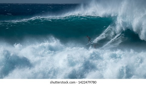 OAHU / USA - DECEMBER 05, 2019: Two surfers sharing the giant wave at the famous Waimea Bay surf spot located on the North Shore of Oahu in Hawaii