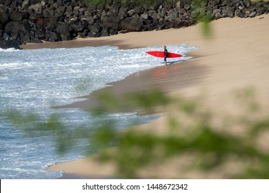 OAHU / USA - DECEMBER 05, 2019: Big wave surfer stands on the sandy beach and going to enter the ocean at the famous Waimea Bay surf spot located on the North Shore of Oahu in Hawaii