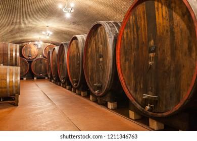 Oak barrels holding wine staged in a winery cellar