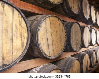 Oak barrels piled for storing alcoholic beverages such as wine, whisky, rum, and etc.