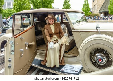 OAK BROOK, IL/USA - JUNE 16, 2019: A mature woman in fashionable period dress beams in the front seat of a 1936 Packard on display at the 51st Annual Father's Day Classic Car Show at Oakbrook Center.