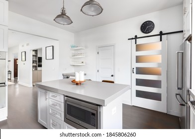OAK PARK, IL, USA - AUGUST 7, 2020: A white kitchen with stainless steel appliances, grey countertops, and hardwood floors through the house. A barn door hangs with light shining through.
