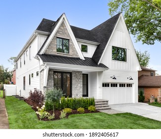 OAK PARK, IL, USA - AUGUST 17, 2020: A new, white modern farmhouse with a dark shingled roof and black windows. The left side of the house has a light rock siding and a covered front porch.