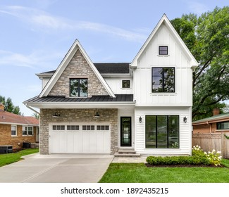 OAK PARK, IL, USA - AUGUST 17, 2020: A new, white modern farmhouse with a dark shingled roof and black windows. The left side of the house is covered in a rock siding.