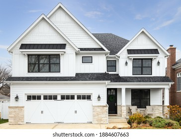 OAK PARK, IL, USA - NOVEMBER 2, 2020: A new, white modern farmhouse with a dark shingled roof and black windows. The bottom of the house has a light rock siding and a covered front porch.