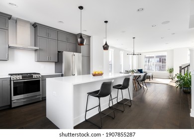 OAK PARK, IL, USA - NOVEMBER 1, 2020: A modern, luxury grey kitchen with a white island looking out towards an open dining room and living room with hardwood floors throughout.