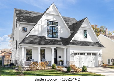 OAK PARK, IL, USA - OCTOBER 28, 2020: A new, white modern farmhouse with a dark shingled roof and black window frames. The bottom of the house has a light rock siding and covered front porch.