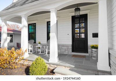 OAK PARK, IL, USA - OCTOBER 28, 2020: A new, white modern farmhouse with a dark wood door with windows, white pillars, a stone floor, and patio furniture.